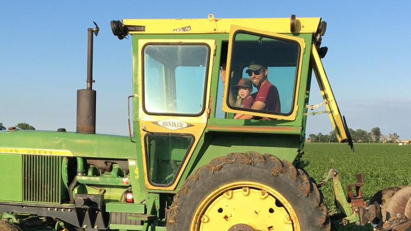 Andy Bartlett and son in a tractor in a field
