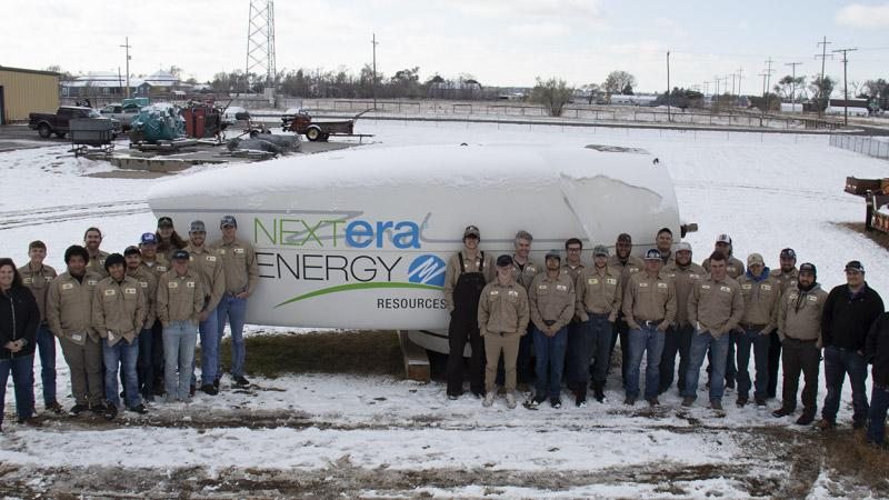 Students and representatives from Nextera Energy posing in front of a nacelle.